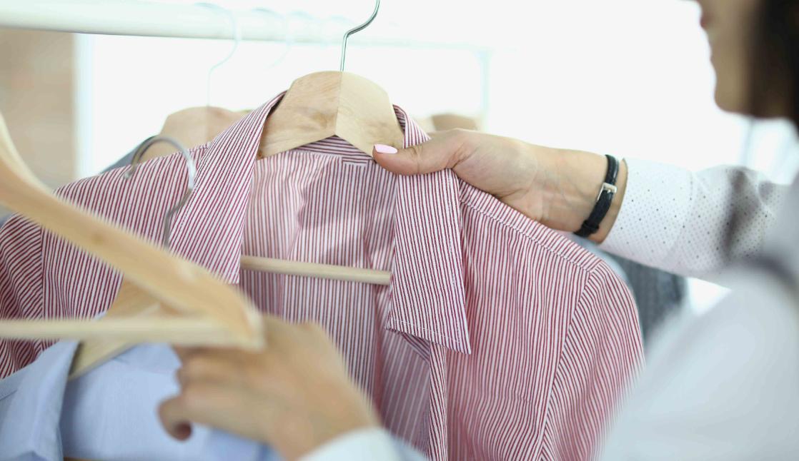 Une femme entrain de regarder des vêtements.